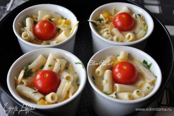 В порционные формочки выложить смесь из макарон. Заполнить формочки на ¾. Залить макароны яичной смесью. В серединку положить по 1–ой помидорки черри и посыпать все кунжутом. Запекать фриттату в заранее нагретой до 200 С духовке, примерно 20 минут.