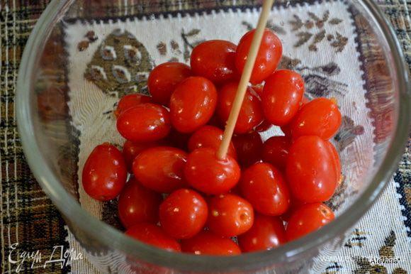 Проткнуть каждую помидорку зубочисткой или деревянным шампурем с 2х разных сторон.