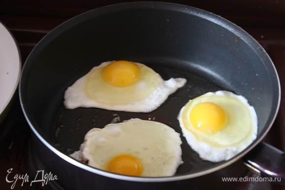Убираем хлеб со сковороды, вытираем ее бумажной салфеткой и пожарим 2-3 яйца, каждое отдельно, чтобы не соприкасались. Готовим их 6-7 минут, так чтобы желток остался жидким.