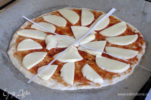 Выложить на тесто моцареллу. Из бумаги вырезать две полоски и выложить на пиццу в виде креста, формируя 4 сегмента.