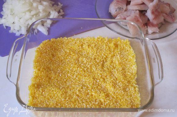 Выложить на дно формы для запекания кукурузную крупу. Посолить, поперчить.