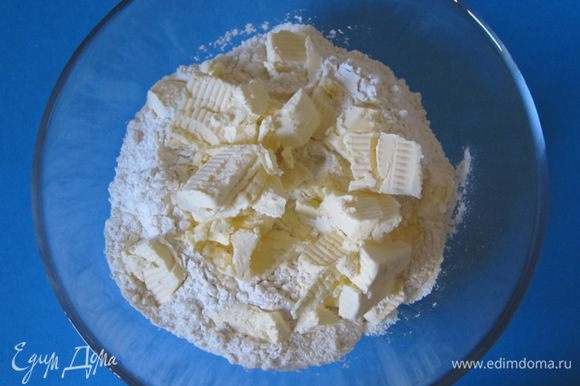 Муку просеять в миску. Сливочное масло нарезать кубиками.