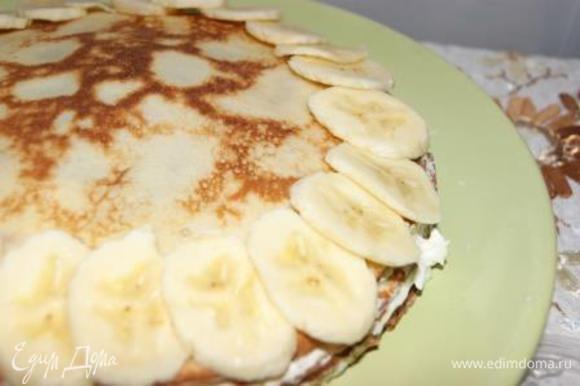 Тем временем, 1 банан нарезать на тонкие дольки, выложить на торт.