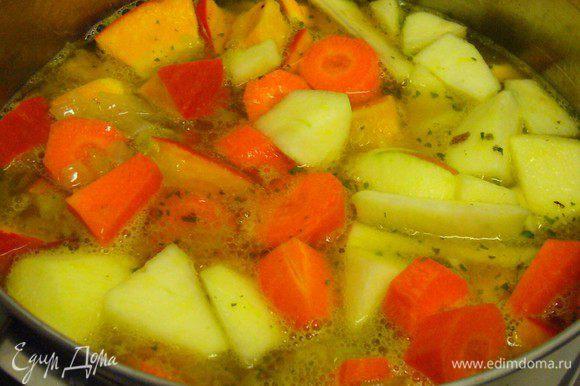 В кастрюлю погружаем тыкву, яблоко, морковь, обжаренный лук и заливаем овощным бульоном. Слегка подсаливаем.
