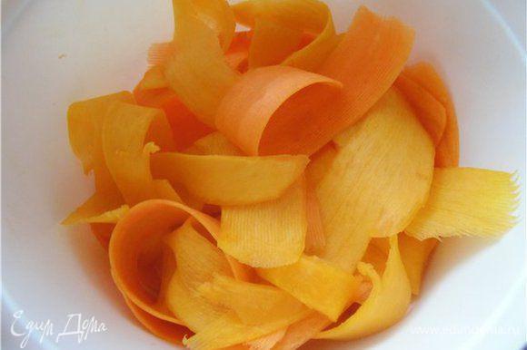 Сырые тыкву и морковь натереть с помощью овощечистки.