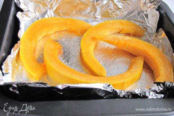 Тыкву нарезать ломтиками, смазать растительным маслом, выложить на противень, застеленный фольгой и запечь в духовке около 30 минут при 180 град.