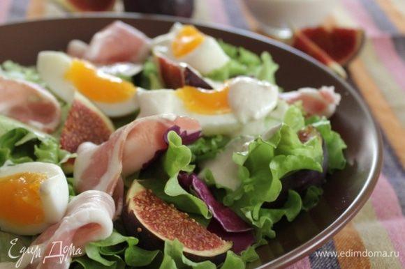 На плоское блюдо выложить смесь салатов и полить их частью соуса. Сверху разложить прошутто, инжир, яйца. Полить салат соусом. Для того, чтобы заправка на салате выглядела презентабельно, можно воспользоваться кондитерским мешком. Присыпать салат зелёным луком. Приятного аппетита!
