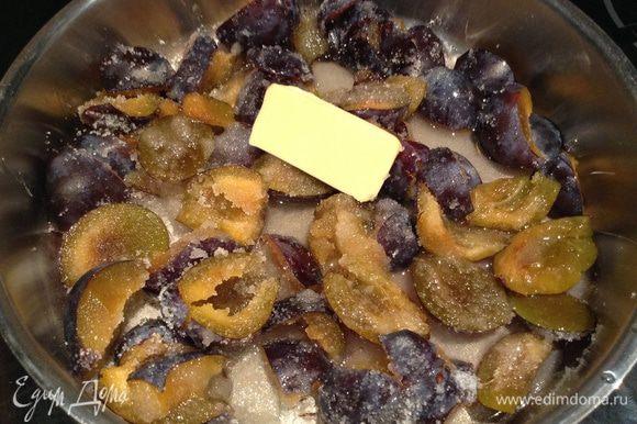 Выложить сливы в сотейник или сковороду с высокими бортиками, добавить сахар, масло (10 г), поставить на плиту на средний огонь и варить, постоянно помешивая, пока масса не загустеет.