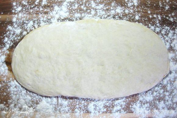 Подошедшее тесто выложить на присыпанную мукой рабочую поверхность и расправить руками в прямоугольник высотой около 3 см.