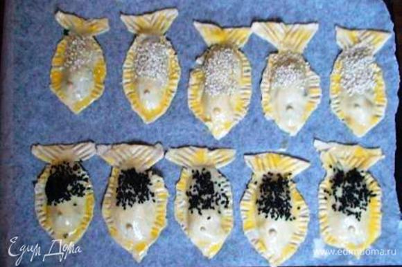 Противень выстелить пергаментом, выложить на него пирожки, смазать их взбитым желтком и присыпать кунжутом.