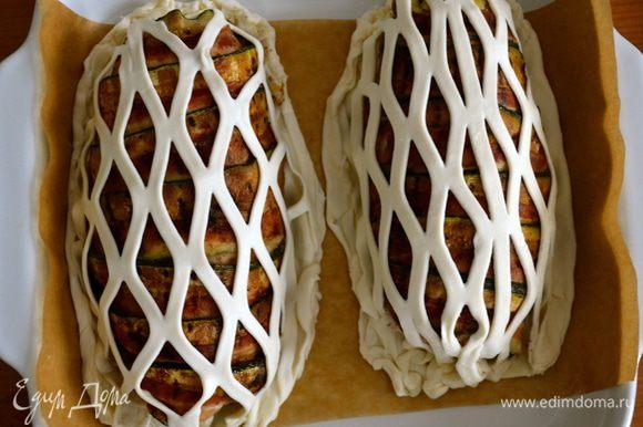 Надрезанное таким образом тесто разрезать на двое. Слегка взбитым яйцом смазать края теста, на котором лежат грудки, накрыть сверху сеточкой и как следует закрепить края. Обе грудки положить в форму для выпечки на пекарскую бумагу.