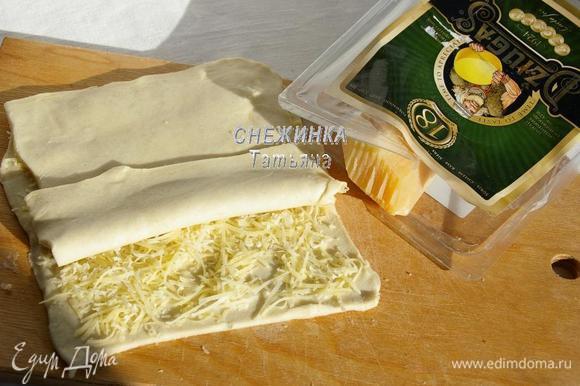 Сыр Джюгас натираем на мелкой тёрке. На одну половину теста распределяем сыр. Накрываем второй половиной. Раскатываем тесто в таком виде снова в прямоугольник по размеру, как в первый раз.