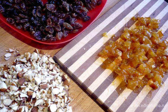 Приготовим начинку. Изюм замочим в кипятке на пару минут, затем сольем воду и обсушим его. Цукаты извлечем из варенья и нарежем кубиками. Орехи порубим. Яблоки очистим, удалим сердцевинку, нарежем дольками.