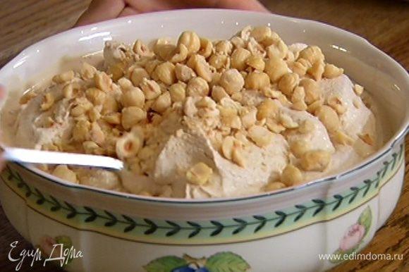 В готовое мороженое добавить измельченные орехи и перемешать. Каждую порцию мороженого украсить оставшимися целыми орехами.