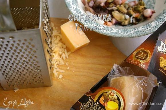 Для рулета пооловину сыра Джюгас натираем на крупной тёрке, вторую половину нарезаем тонкими пластинами. Морской коктейль опускаем в кипяток, даём снова воде закипеть и вынимаем.