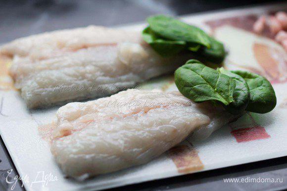 Филе натираем солью и смесью перцев. На хвостовую часть с внутренней стороны выкладываем 4-5 листочков шпината.