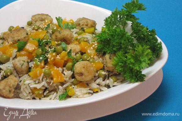 Отварить рис, сбрызнуть оливковым маслом, соединить с тефтелями, обжаренным перцем, консервированным горошком, кунжутом и остальной мелко нарезанной петрушкой. Посолить, поперчить, еще добавить оливковое масло, перемешать.
