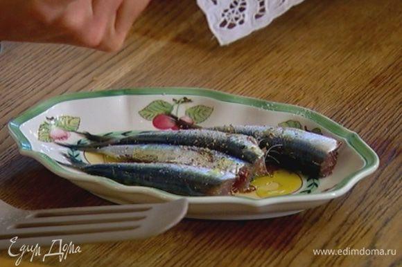 Сардины слегка сбрызнуть оливковым маслом, посолить и поперчить со всех сторон.