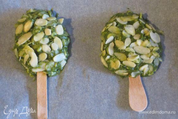 """В чаше миксера соединить салат латук, шпинат, морковь, картофель и измельчить массу. Добавить сыр, яичный желток, посолить и хорошо перемешать. Столовой ложкой взять овощную массу, сформировать """"эскимо"""", вставить деревянные палочки, обвалять в миндальных хлопьях и выложить на противень с пергаментом."""