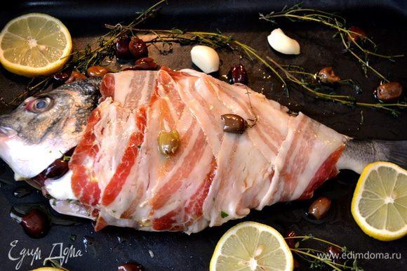 Выложить рыбу в форму для выпечке, соответствующую размеру Вашей дорады. Сбрызнуть рыбку оливковым маслом, посолить, добавить листья тимьяна и зубчики чеснока... Я от себя добавила немного мелких темных оливок (taggiascе). Можно выложить несколько долек лимона.