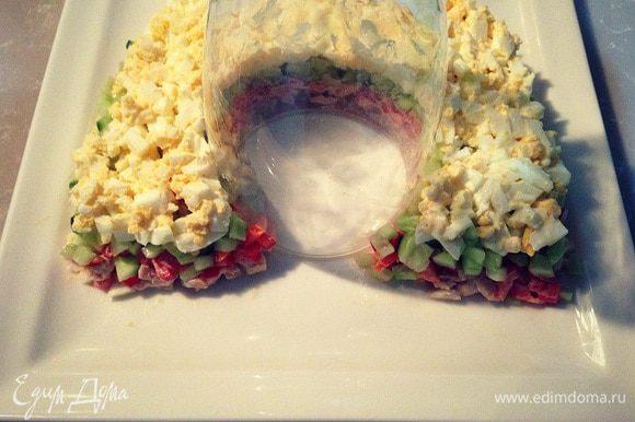 Мелко порубленные яйца смешать с ложкой майонеза и выложить следующим слоем по верх огурцов....