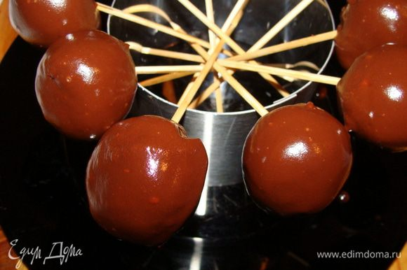 В это время растопить на водяной бане шоколад, можно добавить кусочек сливочного масла (50 г). Шарики нанизать на шпажки, обмакнуть в шоколад, поставить стекать. Как только все шарики окажутся в шоколаде, убрать конструкцию полностью в морозилку еще на 15 минут. Хранить конфетки в холодильнике.