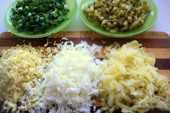 Отварить картофель в мундире и яйца. Почистить от кожицы и скорлупы. Картофель натереть на терке, яйца разделить на белки и желтки и тоже натереть. Зеленый лук и огурец мелко нарезать.