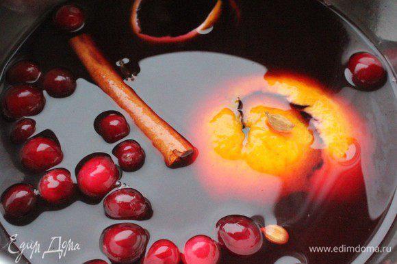 Налить в вино в кастрюлю, положить в него кардамон (раздавить стручки ножом), гвоздику, душистый перец и палочку корицы. Добавить клюкву, апельсиновую и лимонную корки. Медленно прогреть на самом слабом огне. Не кипятить!!! Снять с огня и охладить. Добавить мед (или сахар). Готовый охлажденный глинтвейн процедить.