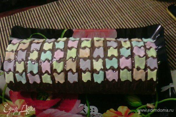 Сверху смазать шоколадом, растопленным на водяной бане и выложить мастикой в виде пазлов.
