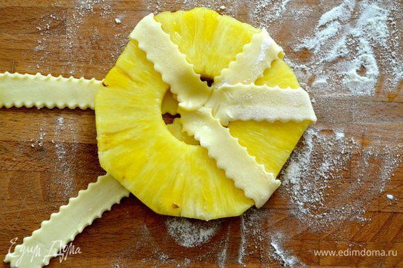Кружочки ананса выложить на тесто и обмотать полосками, завернув концы к центру. Прижать в центре пальцем.