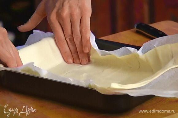 Небольшую форму для выпечки выстелить пищевой бумагой и уложить в нее пласт теста так, чтобы края немного свешивались.