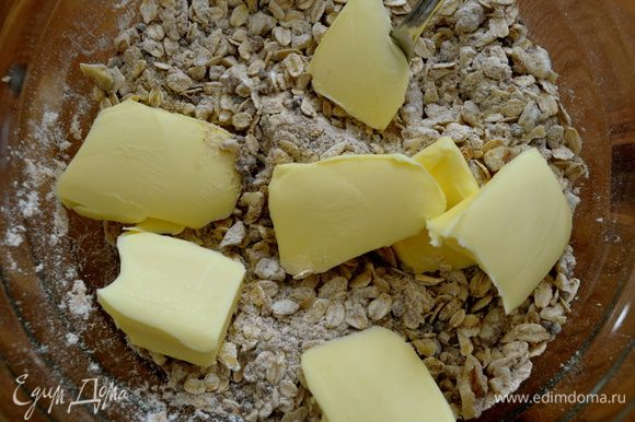 Добавить холодное масло кусочками. Помогая себе вилкой, руками втереть масло в сухую смесь.
