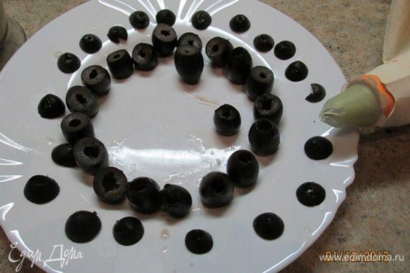 Маслины я купила без косточки. Срезать шляпку у маслины, поставить срезом на тарелку. Крышечку сохранить. Кулинарный мешок начинить муссом из тунца. Начинить маслины муссом, закрыть крышечкой. Приятного аппетита!
