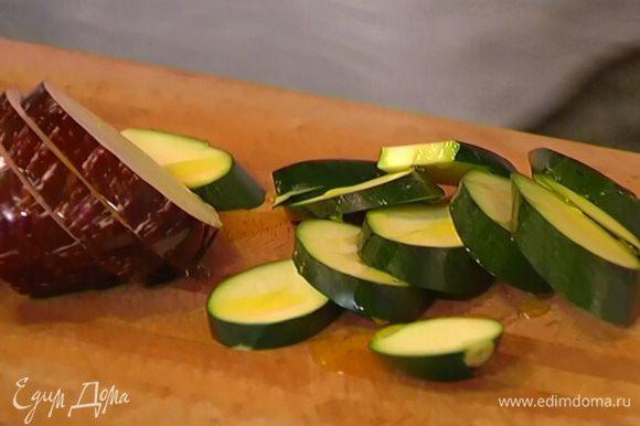 Баклажан и цукини нарезать наискосок толстыми кружками, сбрызнуть оливковым маслом.