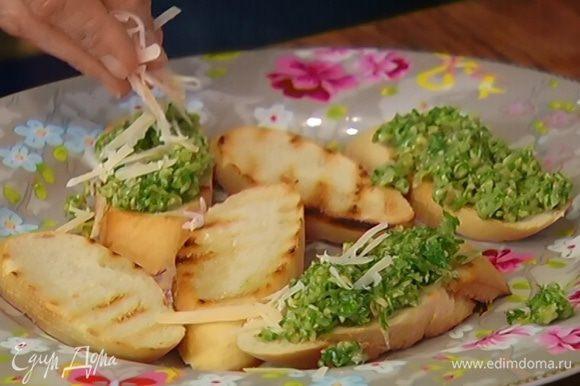 Намазать кростини соусом песто, посыпать оставшимся сыром.