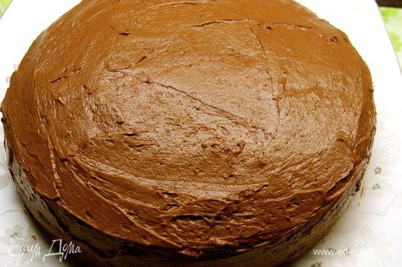 Затем накрыть вторым коржом, снова пропитать сиропом и нанести половину шоколадной глазури. Сверху положить третий корж, пропитать сиропом и покрыть оставшейся половиной глазури, не забыв смазать хорошо бока торта.