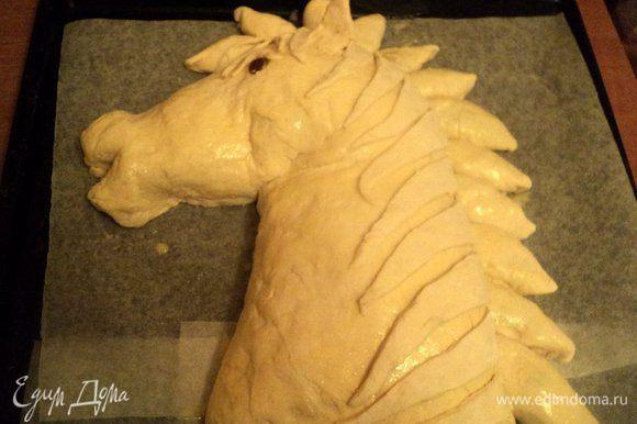 Из пирожков выложить пряди гривы. Из кусочков теста сформировать ушки и глаз лошади, изюминка – зрачок. В таком виде поставить противень с пирогом в теплое место для расстойки и подъема теста. Я ставила в духовку, нагретую до 50 градусов.