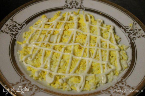 Яйцо натереть на мелкой терке, выложить ровным слоем на блюдо, сверху сделать сеточку из майонеза.