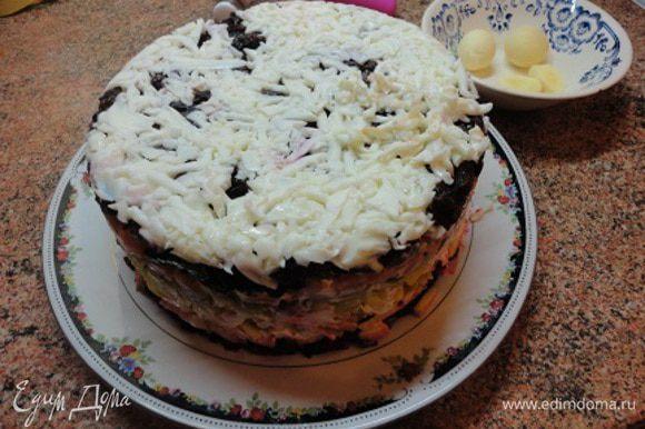 Кольцо от разъемной формы диаметром 18-19 см уложить на блюдо и выложить с него все ингредиенты слоями, смазывая каждый майонезом, в следующей последовательности: свекла, яблоки, картофель, соленые огурцы, морковь, чернослив. Яичные белки натереть на крупной терке и выложить на чернослив. Верх и бока смазать майонезом и верх торта посыпать натертыми на мелкой терке яичными желтками. Бока украсить рублеными орехами, а верх цветами из овощей, входящих в состав салата.