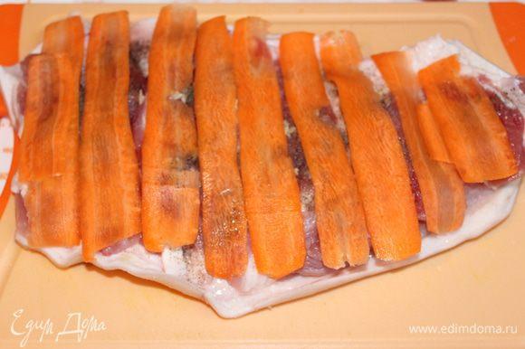 Нарезаем тонко сырую морковь, при помощи овощечистки. Выкладываем полоски на рульку.