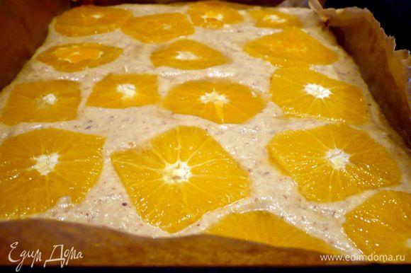 В застеленную бумагой для выпечки форму (у меня прямоугольная, также подойдет и круглая форма диаметром 26 см) выложим тесто, разровняем. Каждый ломтик апельсина опустим в сироп и выложим на тесто. Пирог поставим в духовку на 40 — 45 минут.