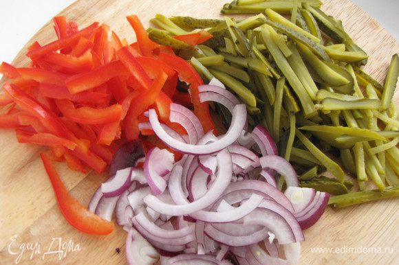 Перец разрезать на четыре части вдоль, почистить от семян, срезать толстые места и нарезать тонкой соломкой. Огурцы также нарезать тонкой соломкой, лук тонкими полукольцами.
