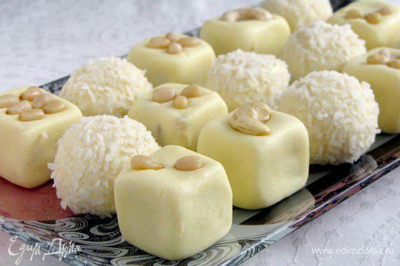 Затем выкладываем кокосовые шарики и молочные кубики на блюдо в произвольном порядке. Кубики украшаем кедровыми орешками.