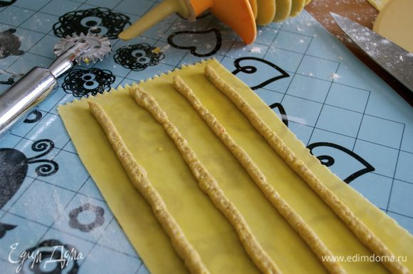 Подготовленный пласт теста смазать с помощью кисточки взбитым яйцом. С помощью кулинарного мешка с тонкой ровной насадкой нанести полоски начинки. 4 или 5, в зависимости от ширины пласта... Я после приспособилась и делала по 5 полосок начинки, экономя и тесто, таким образом.