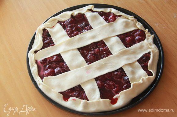 Оставшееся тесто слегка раскатать, нарезать на широкие полоски, выложить на пирог в виде решётки. Полоски и бортики смазать молоком, присыпать сахаром.