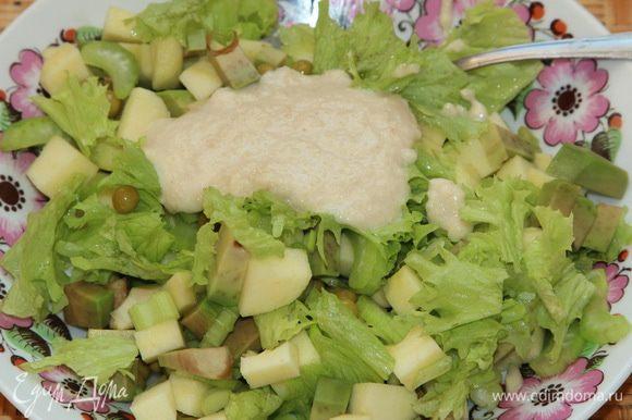 К нарезанным ингредиентам рвем листья салата и добавляем 2 столовые ложки заправки.