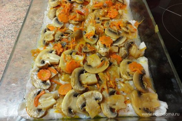 Сверху положить рыбное филе и грибы с оставшимися луком и морковью , влить 2-3 ложки рыбного бульона или просто горячей воды и запекать в разогретой духовке (200 градусов) 20 минут.
