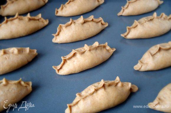 Подготовленные таким образом пироги выложить на противень смазанный маслом. Дать пирогам расстояться в течение 20 минут. Выпекать в заранее разогретой духовке при 180° С около 30 минут. Готовые пироги выложить на решетку.