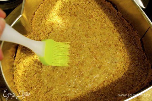 Яичный белок взбить слегка вилкой. Форму с готовым основанием для чизкейка достать из духовки и смазать взбитым белком. Дать остыть.