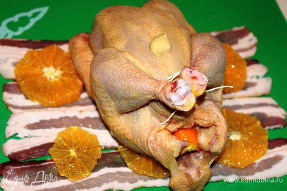 Бекон разложить полоска к полоске, на него выложить апельсин. Ножки цыпленка связать, тушку смазать горчицей (острой), внутрь уложить корки от апельсина и расположить цыпленка на беконе.